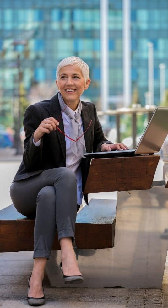 Woman sitting outside an office building looking up temporary staffing jobs on her computer